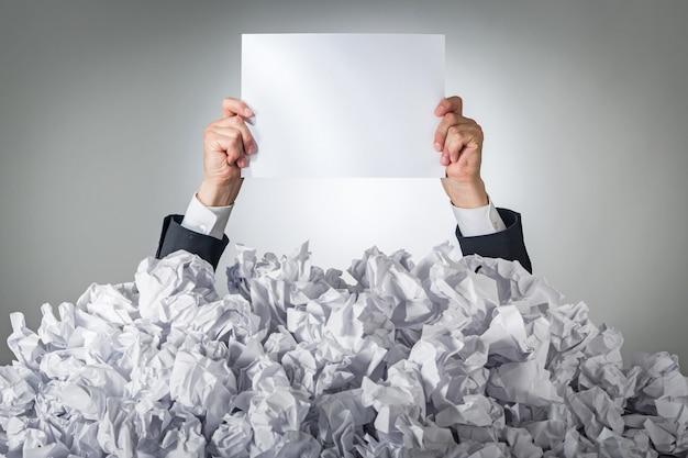 Personne sous une pile de papiers froissés avec les mains tenant une page blanche
