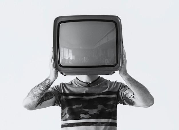 Personne avec tatouage tenant la télévision