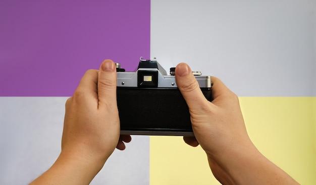 Personne tenant un appareil photo vintage, vue à la première personne.