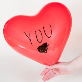 Personne tenant un ballon coeur avec vous inscription