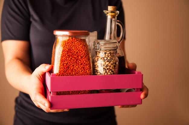 Personne tenant une boîte en bois rose avec des haricots et des lentilles de gruau et de l'huile d'olive.