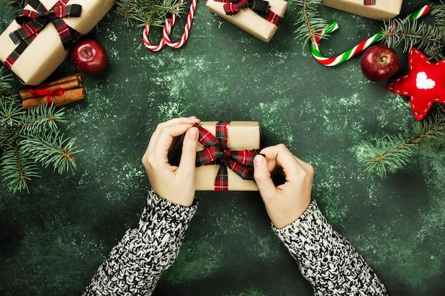 Personne tenant une boîte avec un cadeau pour noël et divers attributs de vacances sur une surface verte