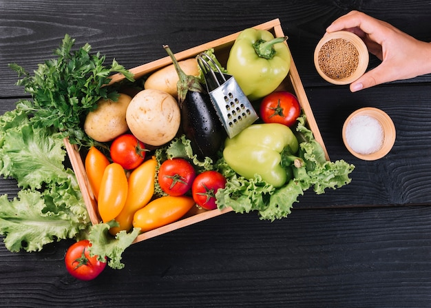 Une personne tenant un bol de graines de moutarde près de légumes frais dans un récipient sur une table en bois noire