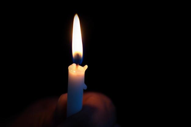 Une personne tenant une bougie dans le noir