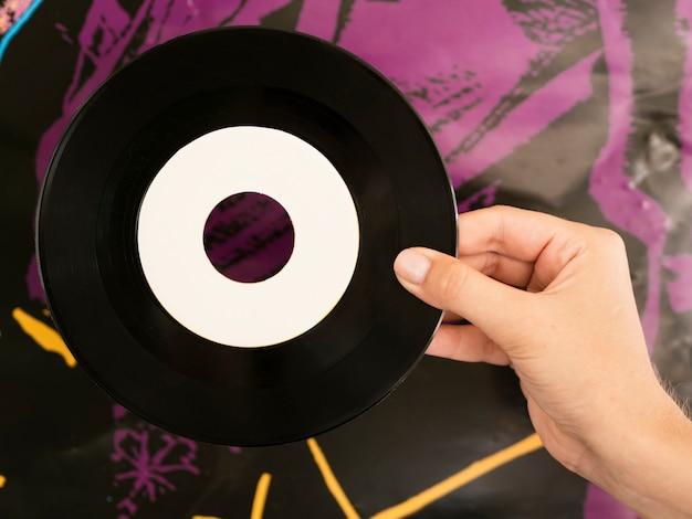 Personne tenant un disque de disque vinyle près d'un mur coloré