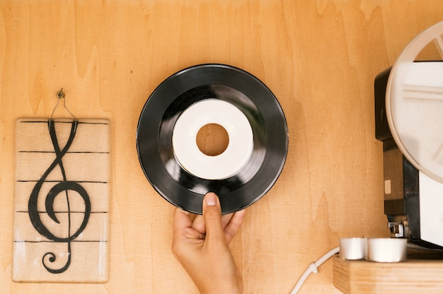 Personne tenant un disque vinyle sur une table en bois
