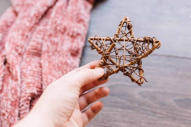 Personne tenant une étoile en bois marron