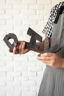 Personne tenant des lettres de bricolage en bois