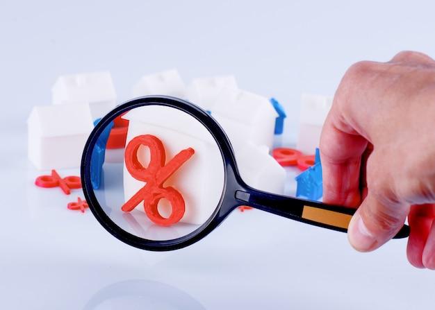 Une personne tenant une loupe et regardant les maisons de jouets et les taux d'intérêt. marché immobilier concept