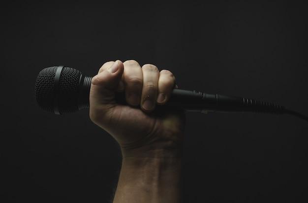Personne tenant un microphone noir