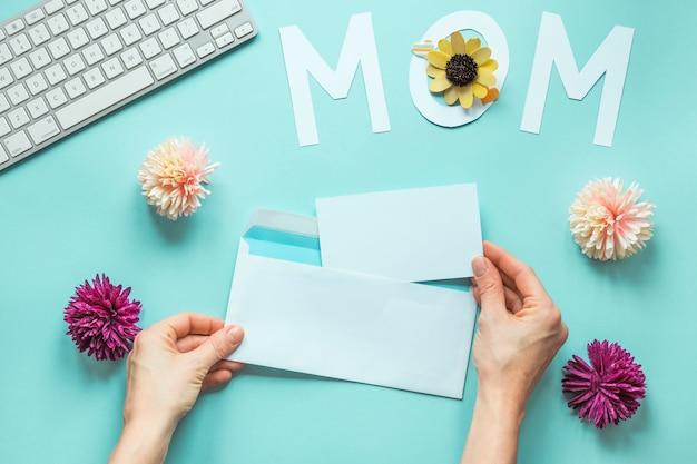 Personne tenant un papier avec enveloppe près de l'inscription de maman