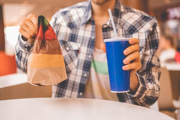 Personne tenant un paquet de restauration rapide et un verre avec déjeuner en public