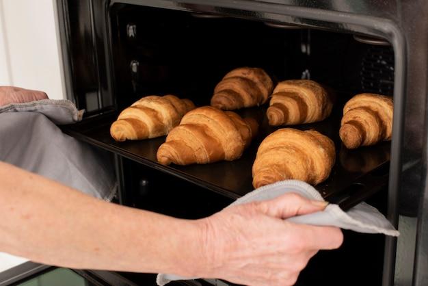 Personne tenant le plateau avec des croissants au four