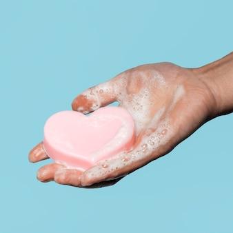 Personne tenant un savon en forme de coeur