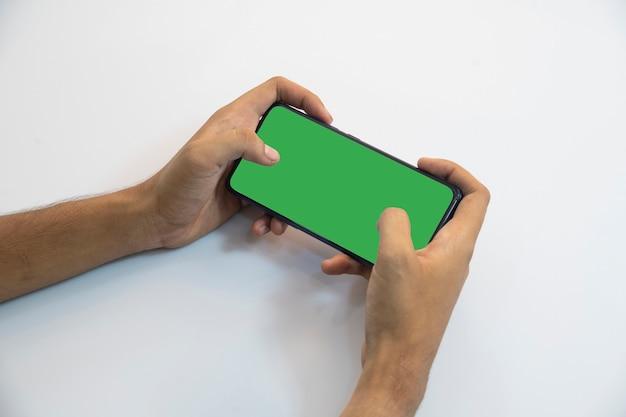 Personne tenant un smartphone avec écran vert