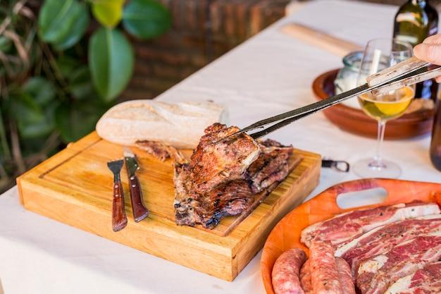 Une personne tenant steak de bœuf grillé frais avec tong sur planche de bois