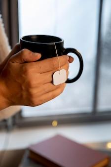 Personne tenant une tasse noire de thé chaud