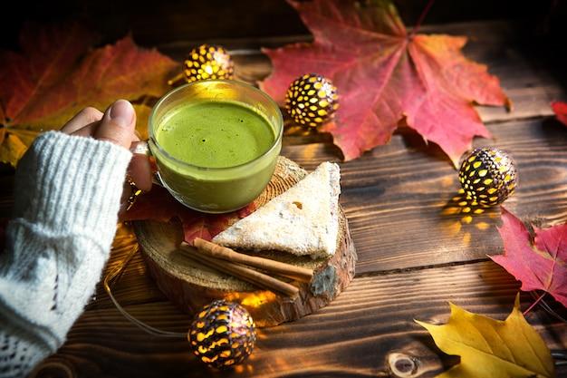 Personne tenant une tasse de thé matcha avec décor d'automne
