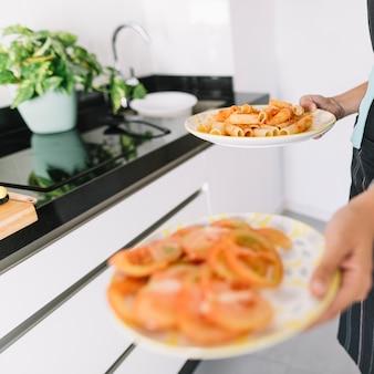 Une personne tenant des tranches de tomate et de délicieuses pâtes sur une assiette