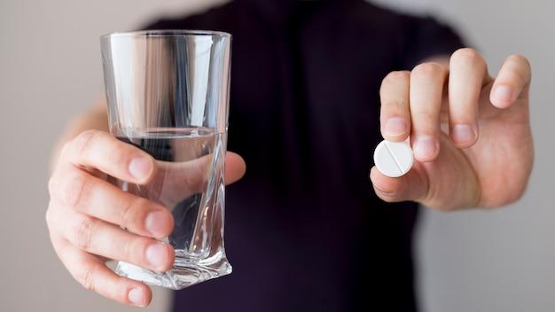 Personne tenant un verre d'eau et une pilule