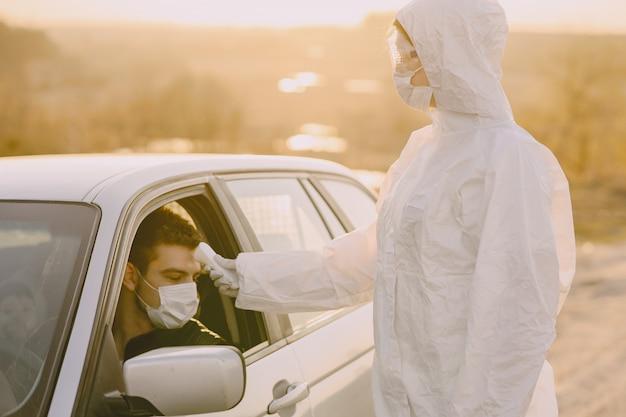 Personne en tenue de protection vérifie la température