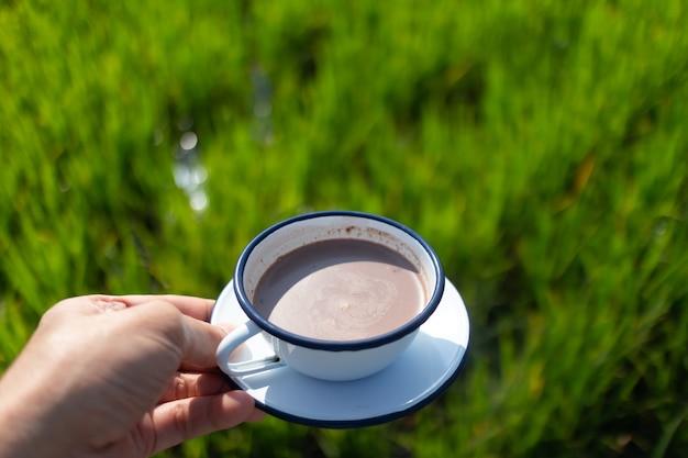 Une personne tient un café avec vue sur une rizière verte dans un concept de détente
