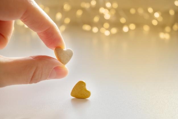 Personne tient en main l'une des deux pilules en forme de coeur sur les lumières floues bokeh