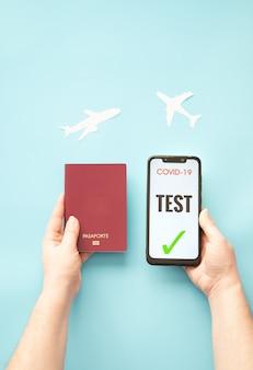 Personne titulaire d'un passeport et d'un smartphone avec un test covid sur fond bleu avec des avions