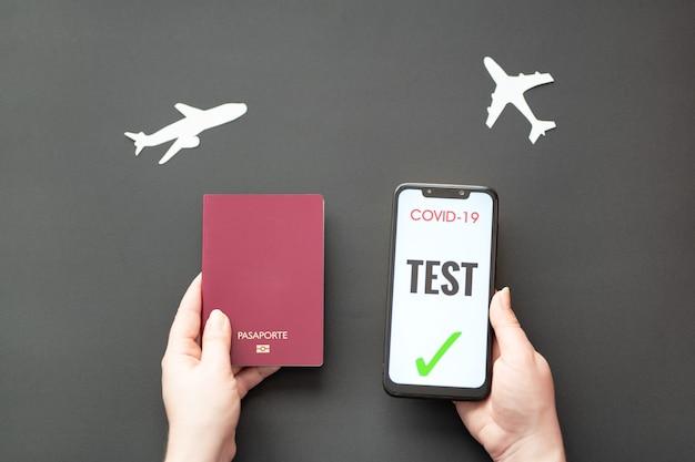 Personne titulaire d'un passeport et d'un smartphone avec un test covid sur fond noir avec des avions