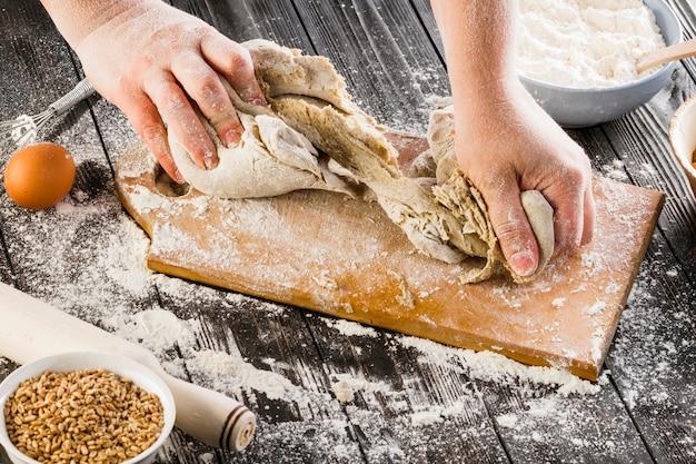Une personne en train de pétrir la pâte avec de la farine sur une planche à découper