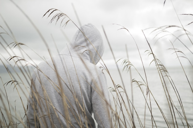 Une personne triste solitaire par derrière avec un sweat à capuche assis près de la mer en pensant à la vie