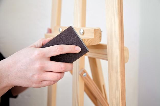 Personne utilisant un bloc éponge de meulage, manipuler un outil abrasif