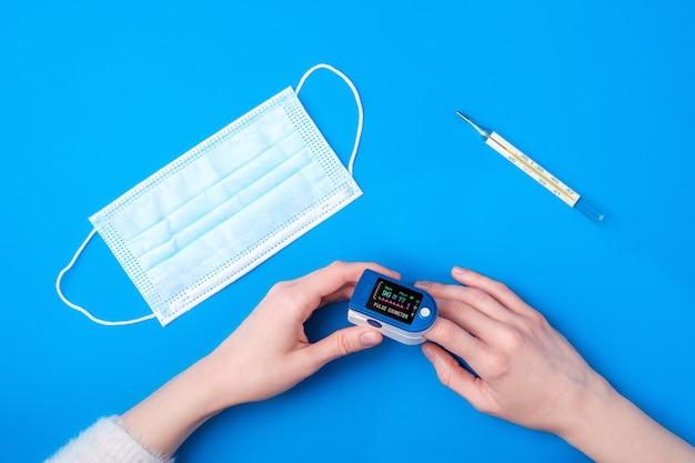 Personne utilisant le dispositif d'oxymètre de pouls sur le doigt près de thermomètre et masque médical, concept de surveillance des soins de santé