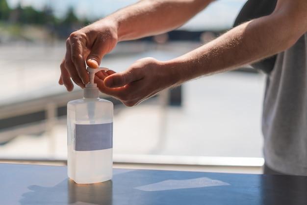 Personne utilisant du gel désinfectant pour les mains en public