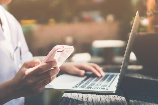 Personne utilisant un ordinateur portable pour travailler et un téléphone mobile pour communiquer