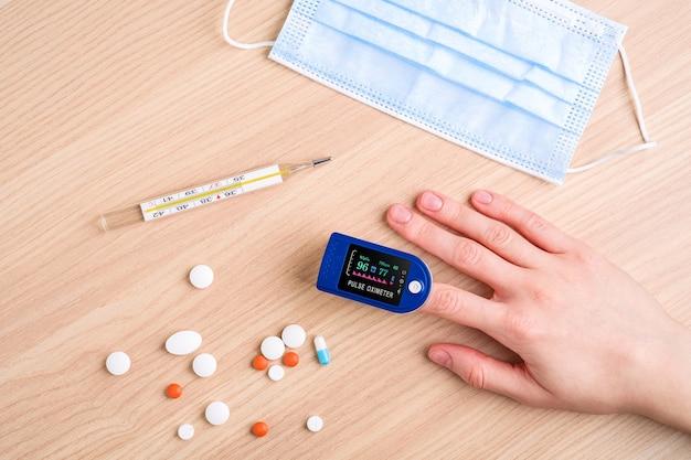 Personne utilisant un oxymètre de pouls près de pilules, thermomètre et masque médical, concept de surveillance des soins de santé