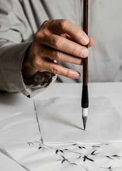 Personne utilisant un pinceau d'encre chinoise