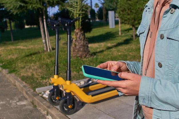 Personne utilisant un smartphone et une application mobile pour la location d'un scooter pour une conduite active mobile rapide à travers la ville