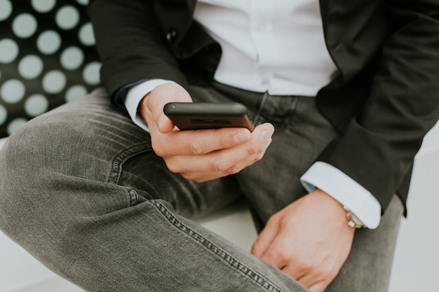 Personne utilisant un smartphone pour consulter les réseaux sociaux alors qu'elle était assise sur le canapé