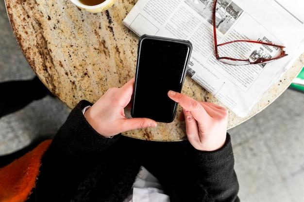 Personne utilisant un smartphone à la table