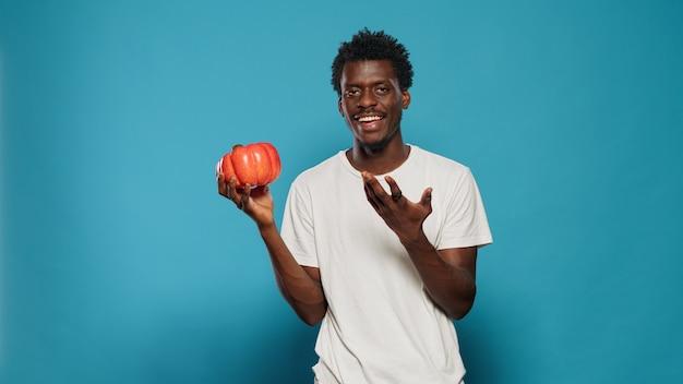 Personne végétalienne tenant le poivron rouge à la main pour cuisiner
