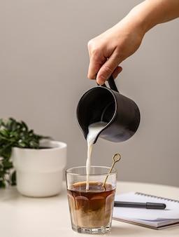Personne versant de la crème dans un verre à café