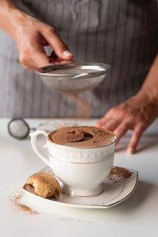 Personne verse du cacao en poudre dans une tasse
