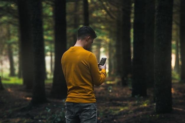 Personne avec une veste jaune et un jean gris regardant le téléphone dans la forêt