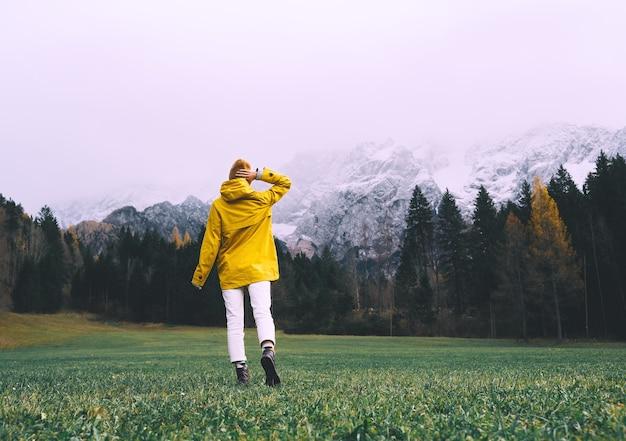 Personne en veste jaune regardant les montagnes voyage d'aventure automne ou hiver en europe