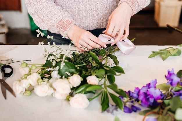 Personne vue de face préparant un bouquet de fleurs