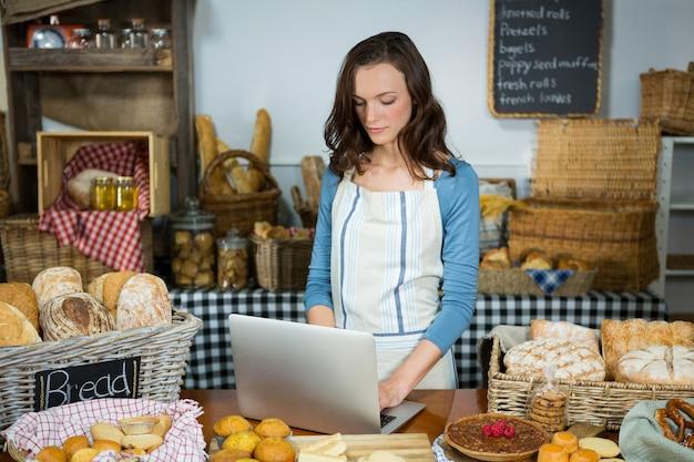 Personnel attentif utilisant un ordinateur portable au comptoir de la boulangerie