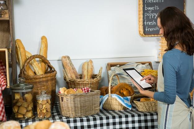 Personnel attentif utilisant une tablette numérique au comptoir de la boulangerie