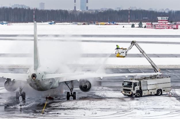 Le personnel au sol pulvérise l'avion, ce qui empêche l'apparition de gel.