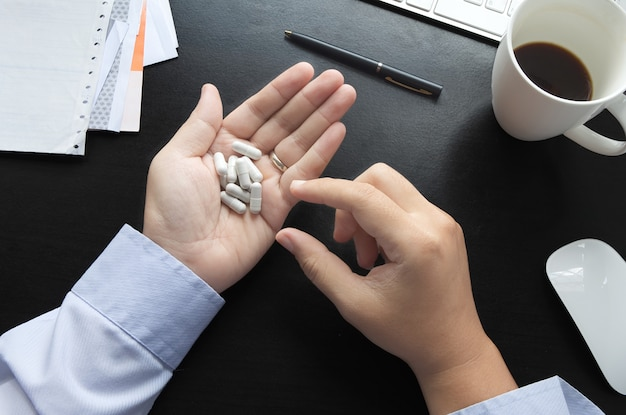 Le personnel de bureau à prendre des médicaments fixer le stress.